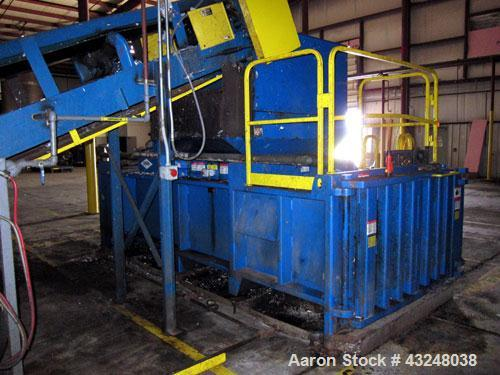 "Used- Excel Manufacturing Horizontal Baler, Model EX62, Carbon Steel. Approximate bale size 30"" x 55"". Top feed with chute. ..."