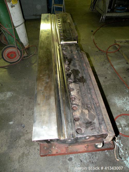 """Used- Titan Sheet Die, 78"""" wide. Approximate 1-5/8"""" diameter back center feed. Mounted on a cart with casters."""